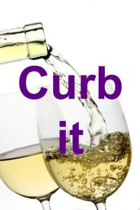 White wine poured in a glass over white background
