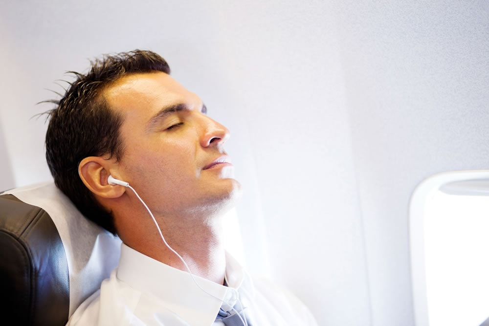 man relaxing on plane