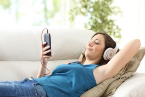 Girl listening music with headphones and smart phone lying on couch at home